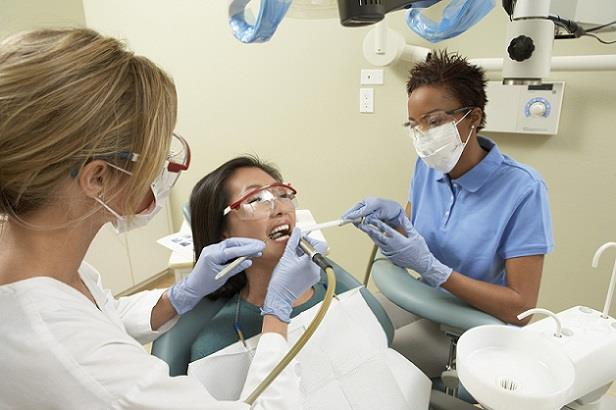 Dentist and dental assistant examining patient