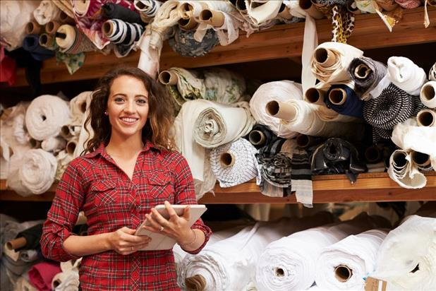 Small business owner posing in front of inventory