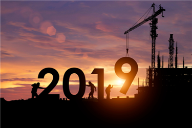 Construction team putting 2019 in place with sunrise as backdrop
