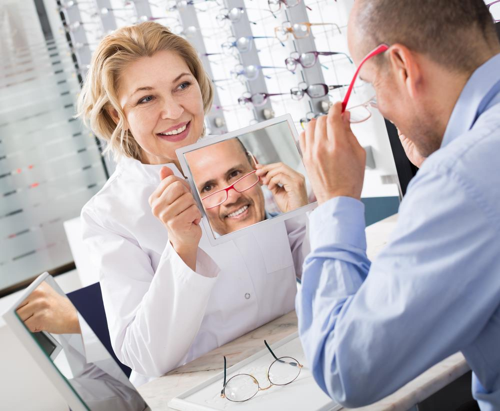 optician holding up a mirror for a customer to see how his new glasses look