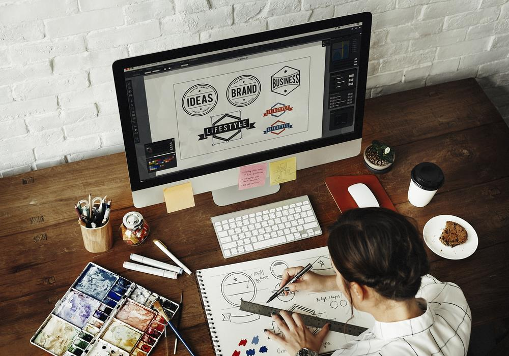 graphic designer at her desk with a computer screen showing logo designs