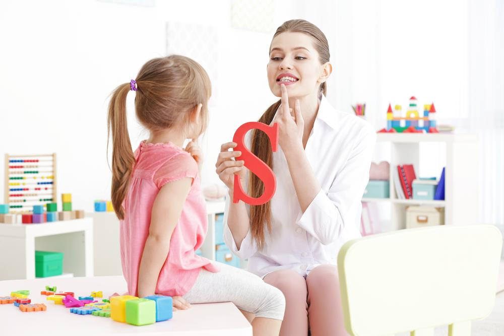Speech-language pathologist meeting with young girl