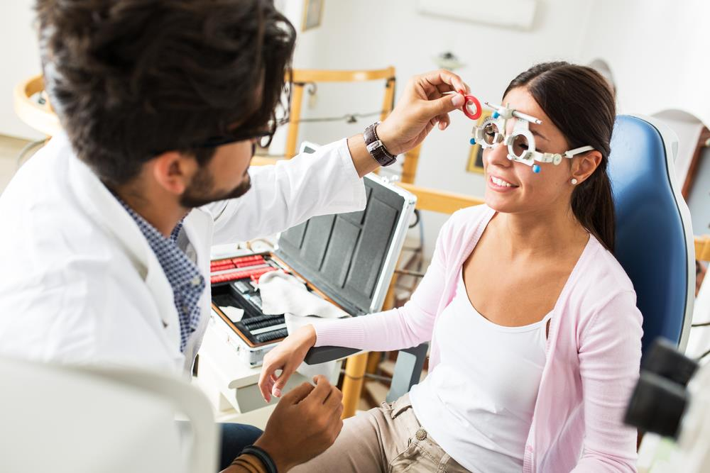 optometrist conducting an eye test on adult patient