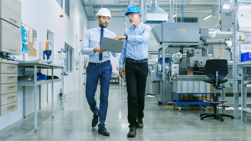 Engineer and plant manager walking through modern manufacturing facility