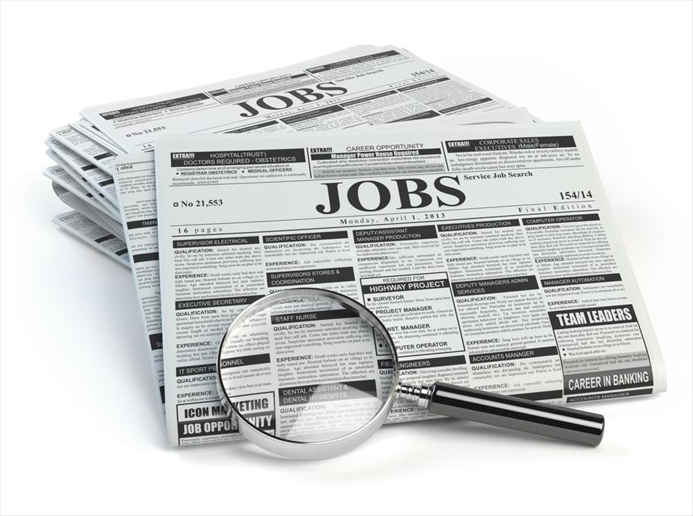 Magnifying glass sits on top of a stack of newspaper job ads