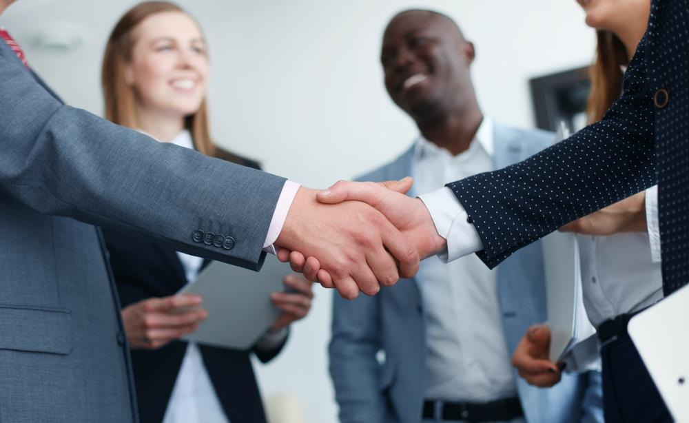 Two employees shake hands while others smile in the background