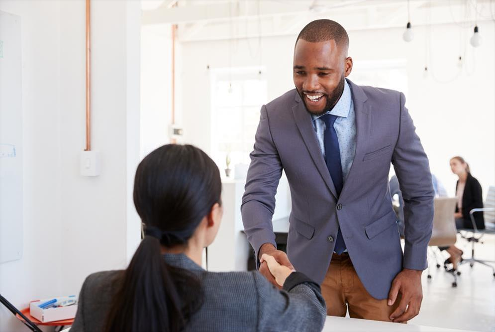 Job candidate shaking hands with hiring manger at interview