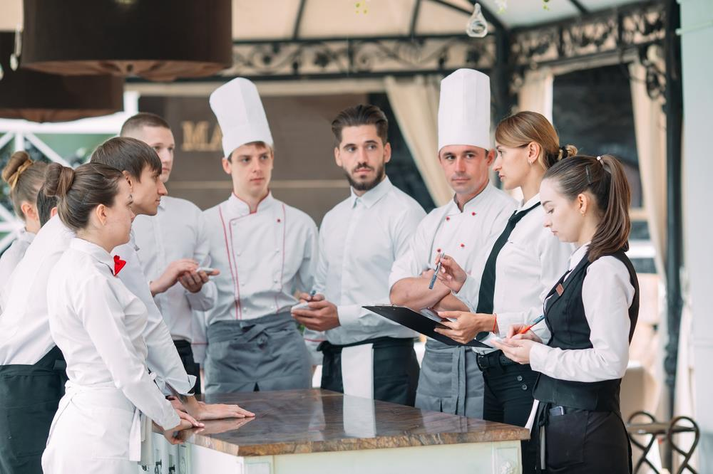 restaurant team and hospitality employees having a meeting