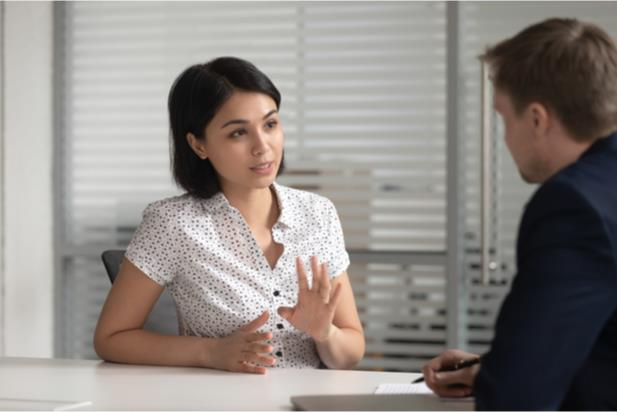 woman speaking to employer at desk