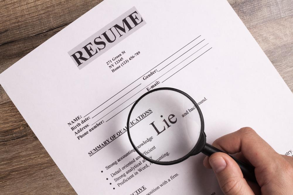 Magnifying glass detecting a lie on a resume.